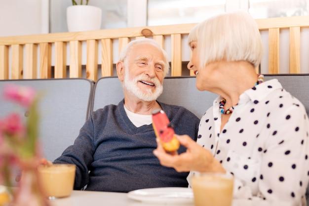 Niski kąt wesoły starszy kobieta trzyma eclair i starszy mężczyzna podziwia żonę
