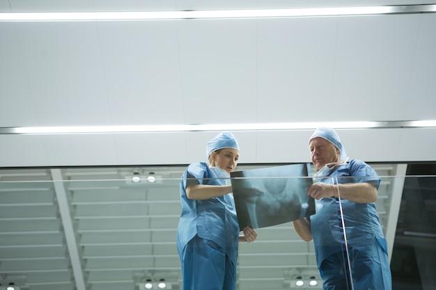 Niski kąt widzenia chirurgów omawiających prześwietlenie w korytarzu