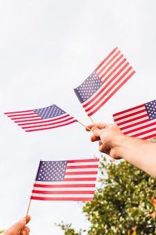 Niski kąt widzenia człowieka ręka trzyma flagi usa