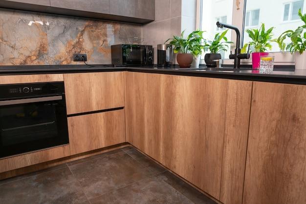 Niski kąt widzenia dopasowanych drewnianych szafek kuchennych z kamiennym blatem i wbudowanym piekarnikiem elektrycznym i płytą grzejną z małym sprzętem agd i zielonymi roślinami doniczkowymi na blacie
