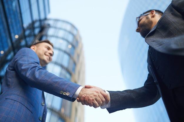 Niski kąt widzenia dwóch młodych biznesmenów, ściskając ręce podczas spotkania w mieście