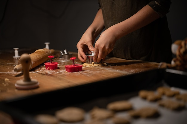 Niski kąt widzenia dziecka naciskając foremkę do ciastek w walcowanym cieście na drewnianym stole.