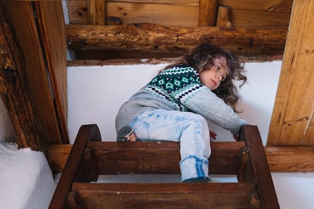 Niski kąt widzenia dziewczyny siedzącej na szczycie klatki schodowej