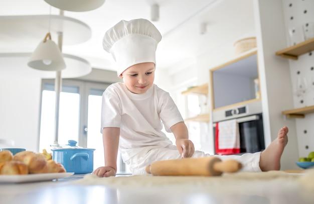 Niski kąt widzenia kaukaskiego dziecka płci męskiej w kapeluszu kucharza siedzącego na kuchennym blacie do pieczenia