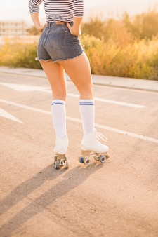 Niski kąt widzenia kobiecej nogi noszenia rocznika rolkach stojących na drodze
