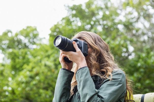 Niski kąt widzenia kobiety fotografowanie aparatem cyfrowym