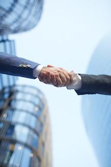 Niski kąt widzenia ludzi biznesu, ściskając ręce do siebie na zewnątrz budynku biurowego