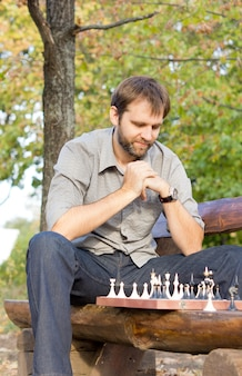 Niski kąt widzenia męskiego szachisty siedzącego na drewnianej ławce w parku kontemplując szachownicę i opracowywania swojej strategii