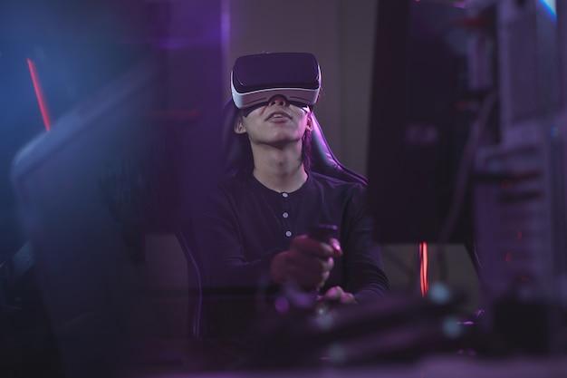 Niski kąt widzenia młodego mężczyzny azjatyckiego noszącego zestaw vr podczas grania w gry wideo przy użyciu zmiany wyścigów w ciemnym wnętrzu cyber, kopia przestrzeń