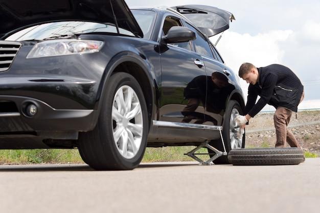 Niski kąt widzenia młodego mężczyzny z przebitą drogą, zmieniającą oponę w jego samochodzie his