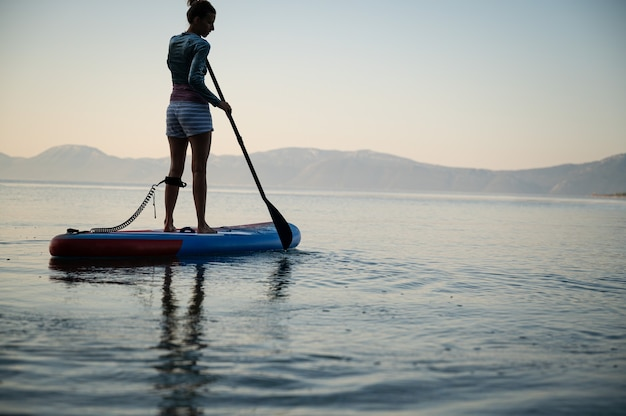 Niski kąt widzenia młodej kobiety ćwiczeń wcześnie rano, wiosłowania na pokładzie sup unoszące się na spokojnej wodzie morskiej.