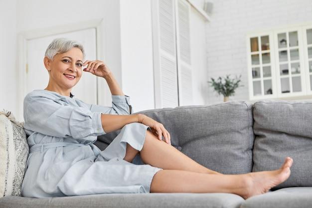 Niski kąt widzenia modnej eleganckiej dojrzałej sześćdziesięcioletniej kobiety rasy kaukaskiej z krótką fryzurą w stylu pixie, relaksującej się w domu, siedzącej na szarej kanapie w swoim przestronnym, przytulnym, czystym salonie, uśmiechając się