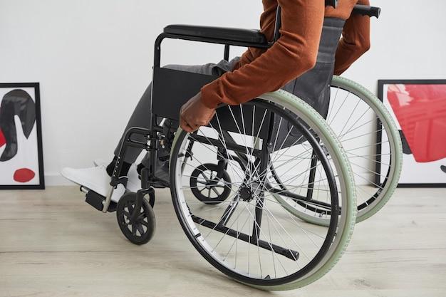 Niski kąt widzenia na nierozpoznawalnego afroamerykanina na wózku inwalidzkim podczas zwiedzania wystawy w galerii sztuki współczesnej,