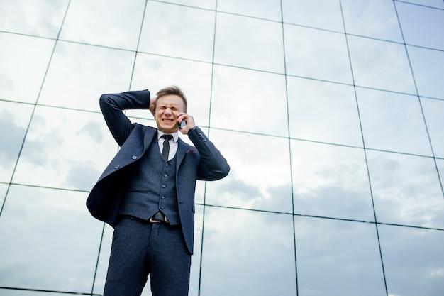 Niski kąt widzenia podkreślił młody biznesmen rozmawia na smartfonie w mieście na zewnątrz. stojąc na tle centrum biznesowego