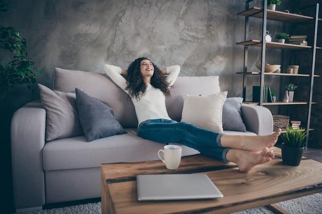 Niski kąt widzenia portret szczupłej szczupłej, smukłej, wesołej marzycielskiej dziewczyny siedzącej na kanapie odpoczywającej w nowoczesnym industrialnym loftowym stylu salonu w pomieszczeniu