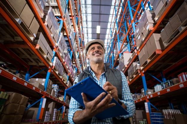 Niski kąt widzenia pracownika uśmiecha się i trzyma schowka