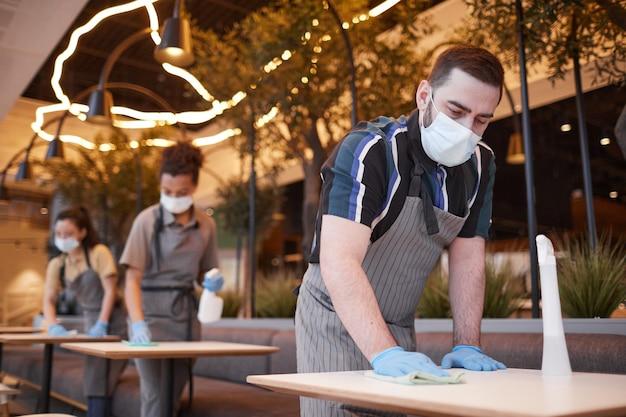 Niski kąt widzenia pracowników noszących maski w rzędzie podczas czyszczenia stołów we wnętrzu kawiarni, koncepcja bezpieczeństwa covid, miejsce kopiowania