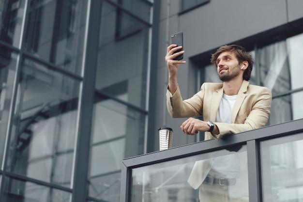 Niski kąt widzenia przystojnego mężczyzny w formalnym stroju, który ma czat wideo na smartfonie, stojąc na balkonie centrum biurowego