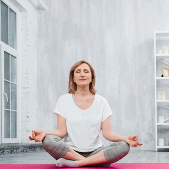 Niski kąt widzenia starszy kobieta robi medytacji w domu
