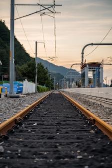 Niski kąt widzenia torów kolejowych i słupa elektrycznego podmiejskiego na stacji