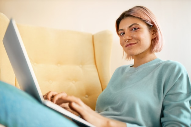 Niski kąt widzenia uroczej stylowej studentki odrabiającej lekcje za pomocą zwykłego laptopa, siedząc na kanapie, grając na klawiaturze, korzystając z szybkiego bezprzewodowego połączenia z internetem. technologia i gadżety elektroniczne