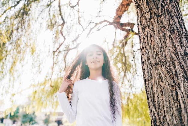 Niski kąt widzenia uśmiechnięta dziewczyna stoi pod drzewem w słońcu