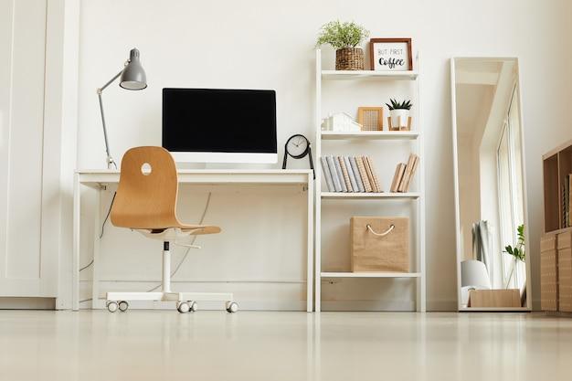 Niski kąt widzenia w całkowicie białym nowoczesnym wnętrzu, z naciskiem na puste miejsce pracy w domowym biurze