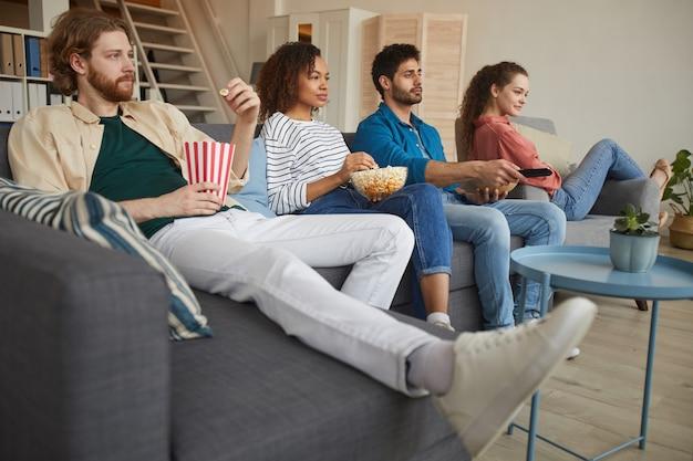 Niski kąt widzenia wieloetnicznej grupy przyjaciół razem oglądających telewizję, siedząc na wygodnej kanapie w domu i delektując się przekąskami
