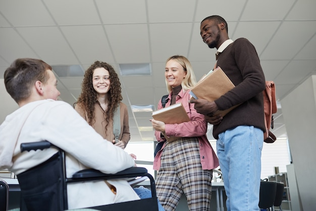 Niski kąt widzenia wieloetnicznej grupy studentów rozmawiających z młodym mężczyzną na wózku inwalidzkim podczas wspólnej nauki w bibliotece uczelni