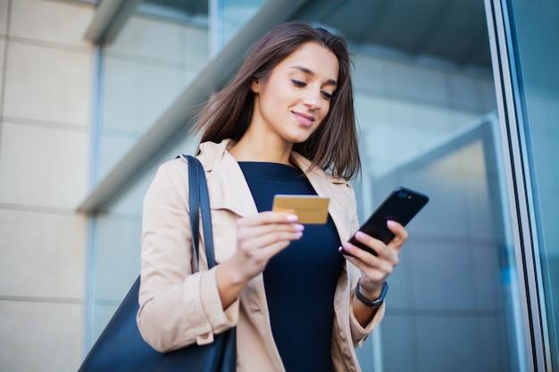 Niski kąt zadowolonej dziewczyny stojącej w hali lotniska, używa do płatności złotej karty kredytowej i telefonu komórkowego