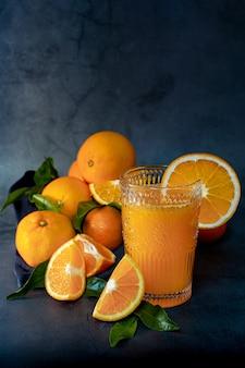Niski klucz obrazu szklanki świeżego soku pomarańczowego obok zestawu pomarańczy gotowych do wyciśnięcia