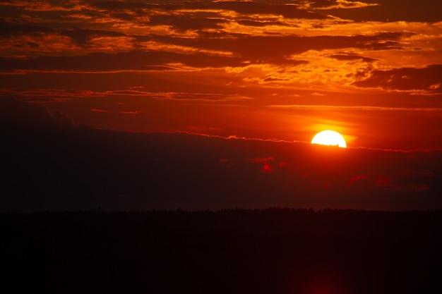 Niski kluczowy zachód słońca nad jeziorem. burgundowe niebo. słońce chowa się za pasem chmur. jest miejsce na kopię.