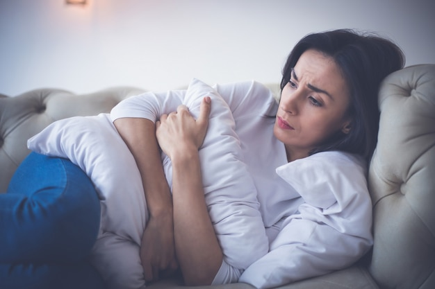 Niski poziom energii. zbliżenie młodej dziewczyny, która leży w łóżku i przytula poduszkę, czując gorączkę.