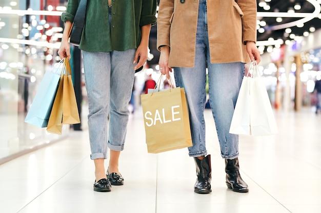 Niski przekrój dwóch młodych kobiet w strojach codziennych, niosących papierowe torby pełne zakupów, idących wzdłuż witryny sklepowej w czarny piątek