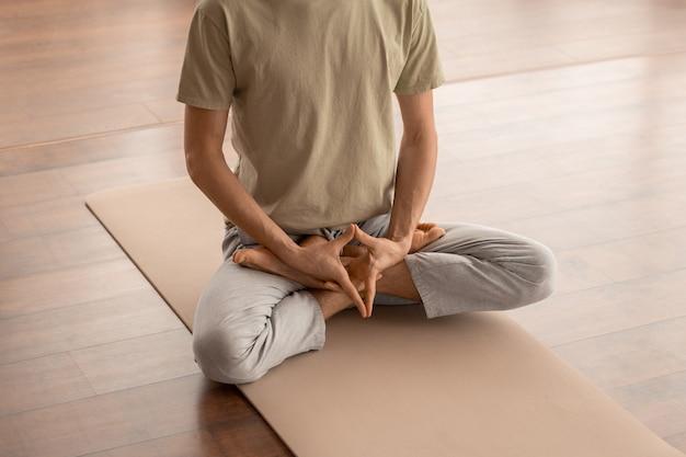 Niski przekrój młodego mężczyzny w sportowej odzieży, siedzącego na macie i trzymającego ręce między skrzyżowanymi nogami podczas medytacji w domu