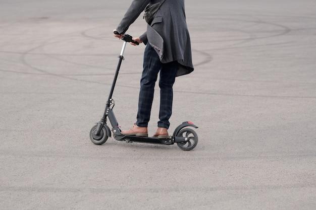 Niski przekrój młodego współczesnego biznesmena w casualwear stojącej na skuterze elektrycznym podczas poruszania się asfaltową drogą do pracy