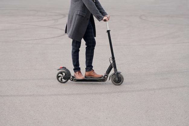 Niski przekrój młodego współczesnego biznesmena w płaszczu, spodniach i butach stojących na skuterze elektrycznym, poruszając się rano do pracy