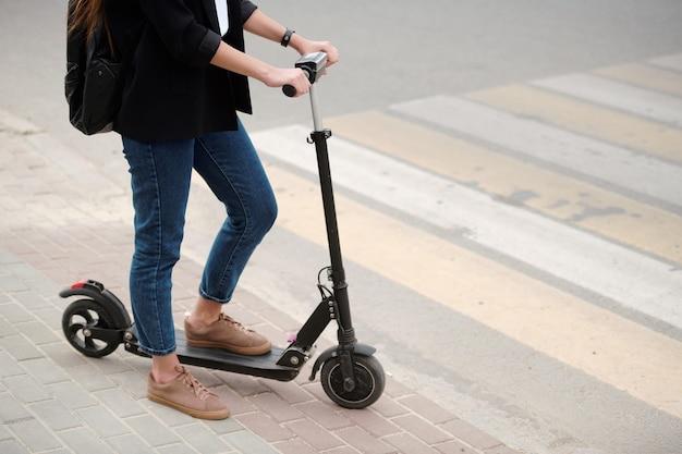 Niski przekrój młodej kobiety w dżinsach i czarnej kurtce, trzymając jedną nogę na skuterze elektrycznym, stojąc przy drodze z przejściem dla pieszych