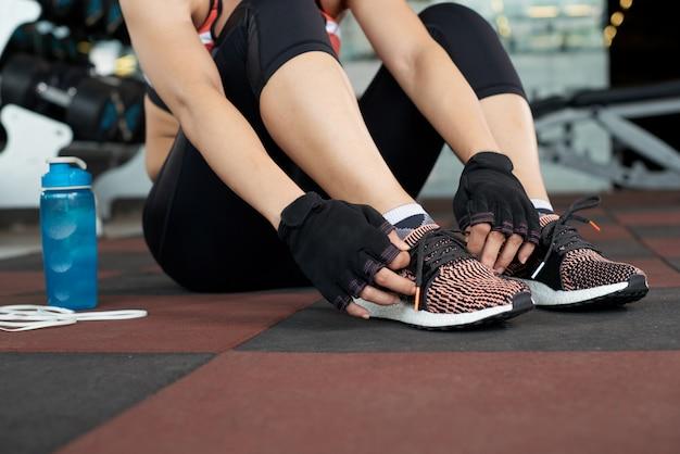 Niski przekrój nierozpoznawalnej kobiety w odzieży aktywnej siedzącej na podłodze sali gimnastycznej, wiążącej sznurówki i przygotowującej się do treningu