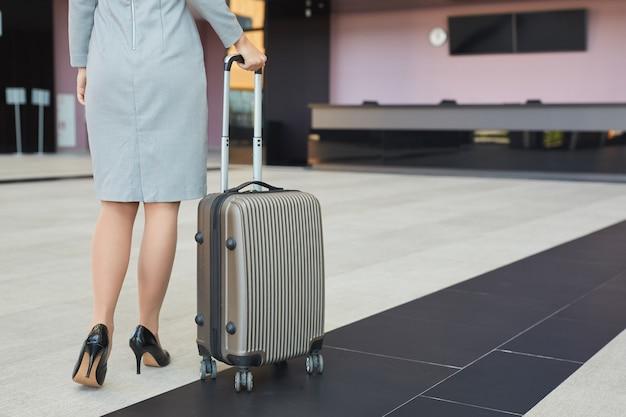 Niski przekrój portret eleganckiej młodej kobiety w szpilkach spacerującej z lotniskiem z walizką,