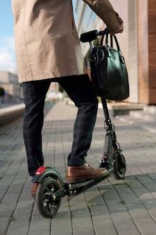 Niski przekrój współczesnego eleganckiego biznesmena z czarną skórzaną torebką stojącą na skuterze elektrycznym w środowisku miejskim
