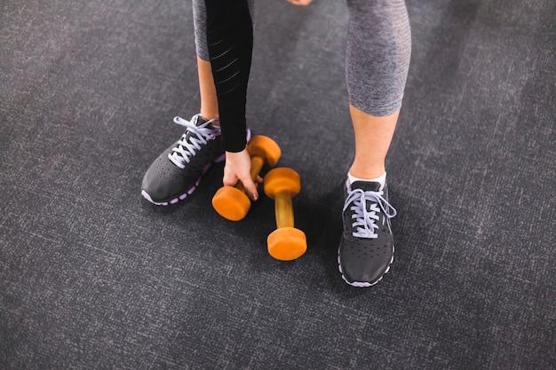 Niski sekcja widok kobiety zrywania dumbbell w gym
