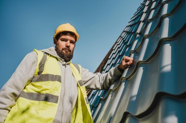 Niski widok człowieka pracującego na dachu z wiertłem
