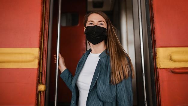 Niski widok kobiety stojącej przy wejściu do pociągu