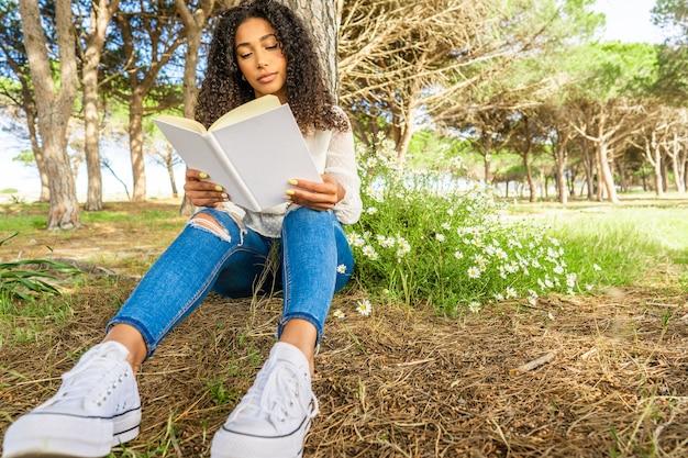 Niski widok z przodu afroamerykańskiej kręconej brunetki w niebieskich dżinsach i białych tenisówkach, siedzącej pod drzewem w sosnowym lesie w pobliżu morza, czytającej książkę obok krzaka stokrotek, bawiącej się opowieściami o miłości