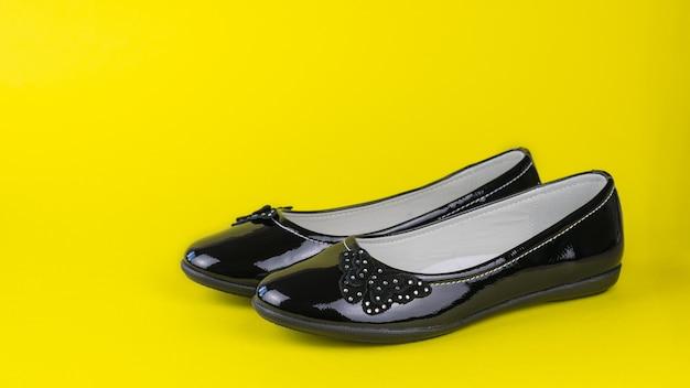 Niskie buty damskie moda na żółtym tle. modne buty do szkoły.