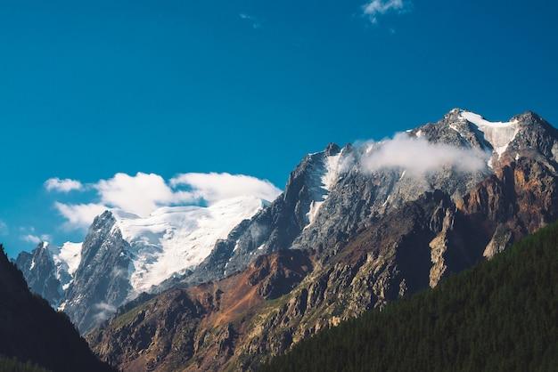 Niskie chmury i mgła na szczycie pasma górskiego. lodowiec pod jasnym niebieskim niebem.