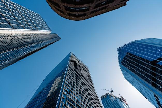Niskie ujęcie nowoczesnych szklanych budynków i drapaczy chmur w pogodny dzień