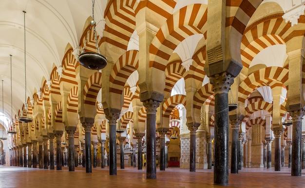 Niskie ujęcie przedstawiające wzorzyste kolumny ustawione w jednej linii wewnątrz majestatycznej katedry w hiszpanii