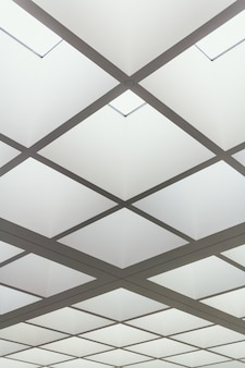 Niskie ujęcie sufitu budynku wykonanego z jasno oświetlonych kwadratów